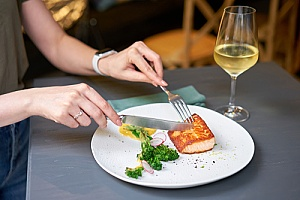 a woman eating salmon at a restaurant that is covered by spoilage and liability insurance