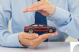 a business man holding a small car covered by commercial auto insurance