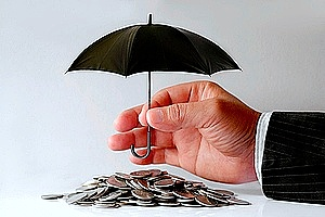 a hand holding a small umbrella covering coins to symbolize insurance coverage