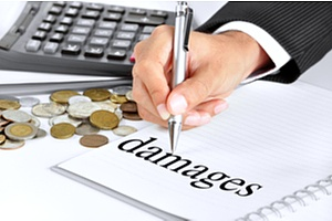 a hand writing the word damages in a notebook to determine damages from a commercial car accident