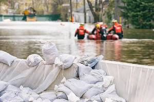 Flood Protection Sandbags with flooded street in the background.Flood insurance can protect a home or business.