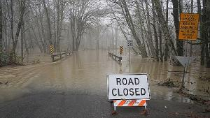 Road closed warning sign on the edge of a flooded street