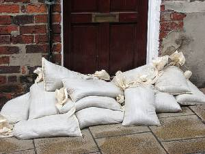 Sandbags stacked as flood barrier in front of door used in place of flood insurance for renters
