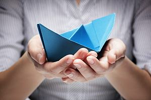 Boat insurance agent holding paper boat
