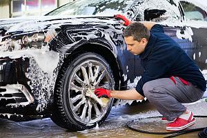 Car wash employee washing wheels