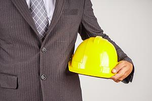 Construction insurance agent holding helmet