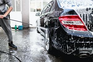 Employee at car wash with hose