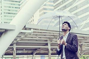 Man holding umbrella in rain