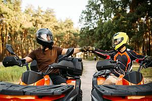 Riders fist bumping on ATVs