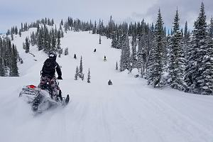 Snowmobile rider going down slopes