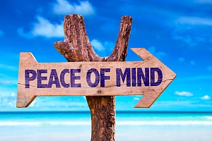 the words peace of mind on a large wooden stick sign on a beach
