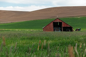 barn with a car that is covered by farm and ranch insurance