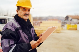 Contractor covered with General Contractor Insurance Wearing Yellow Holding List