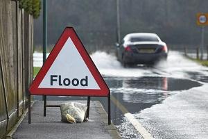 Flood Signboard Near Road needing commercial flood insurance