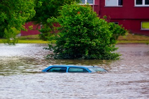 blue car having commercial flood insurance drowned in water