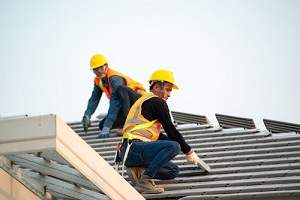construction worker with construction insurance using nail gun to install new roof