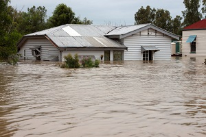 timber country home with water up the windows of building with commercial flood insurance