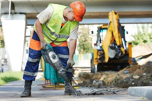 worker with pneumatic hammer drill equipment breaking asphalt at road needing construction insurance