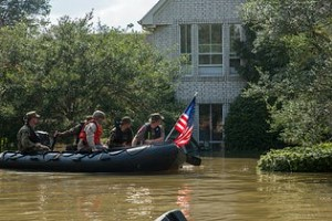 flood rescue team looking at a house