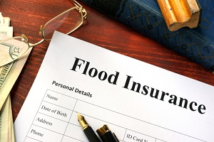flood insurance form on a table with a book with info on flood insurance for commercial property